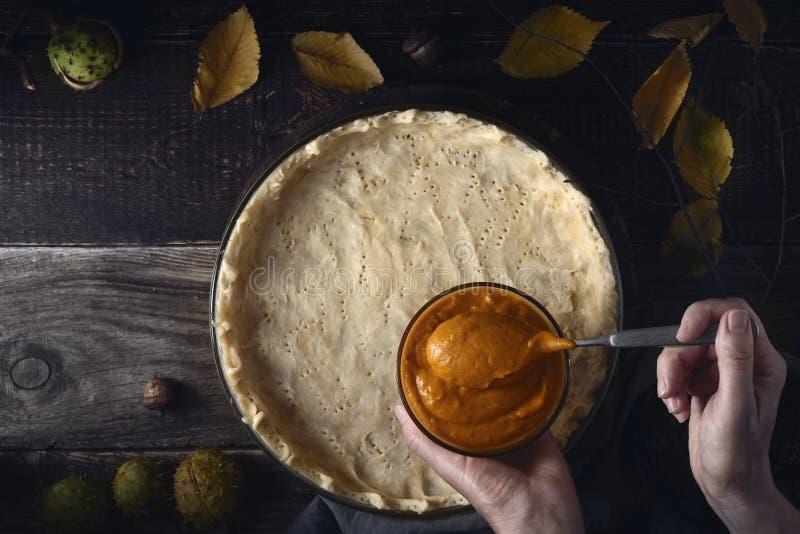 把南瓜纯汁浓汤放在南瓜饼顶视图的面团上 库存图片