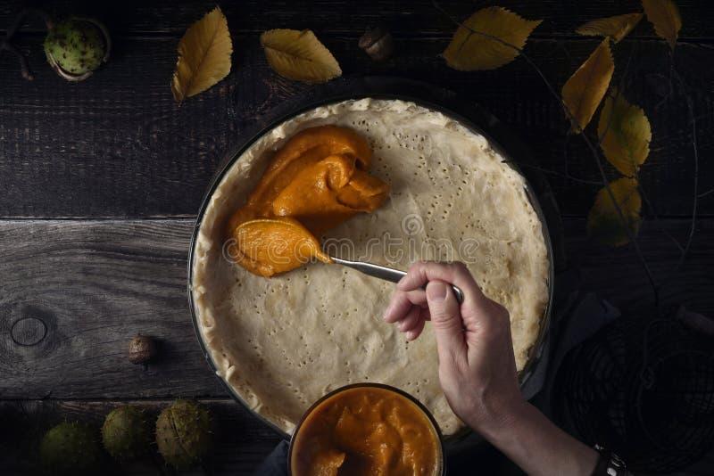 把南瓜纯汁浓汤放在水平的南瓜饼的面团上 免版税图库摄影