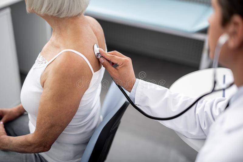 把听诊器放的专业医生在患者上皮肤  库存图片