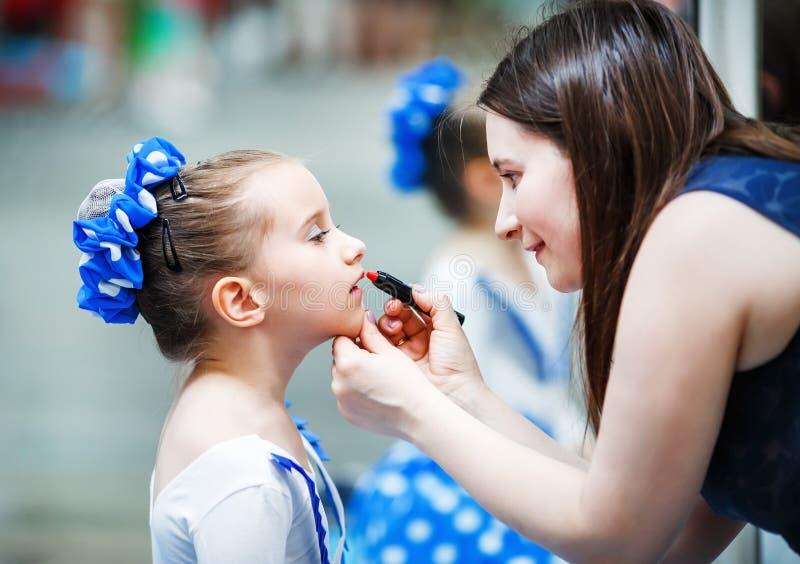 把唇膏放的母亲在她的女儿上 库存照片