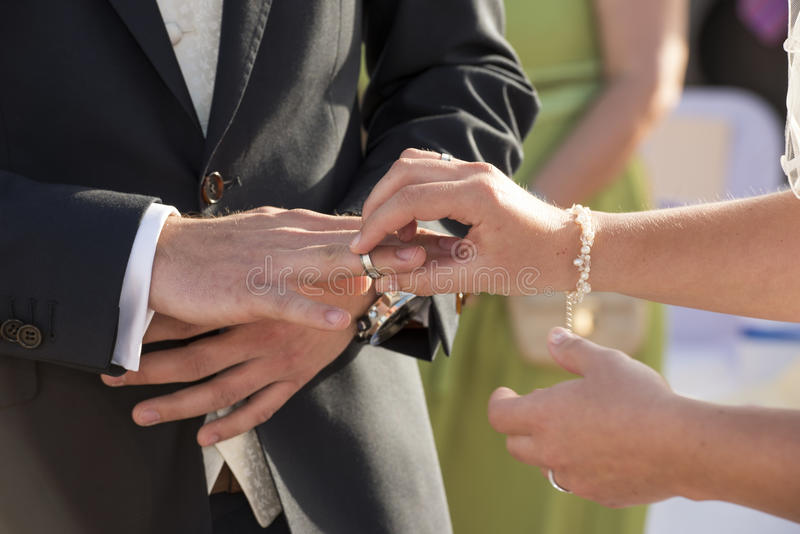 把圆环放的新娘在新郎手指上 免版税库存图片