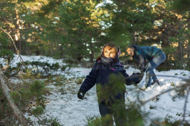 把在山坡的女孩雪球扔出去在一个冷的冬天da 库存照片