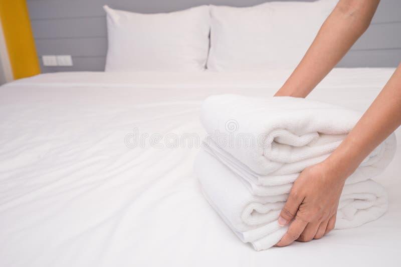 把堆新鲜的白色毛巾放的手特写镜头在床单上 客房服务佣人清洁旅馆客房 免版税库存照片