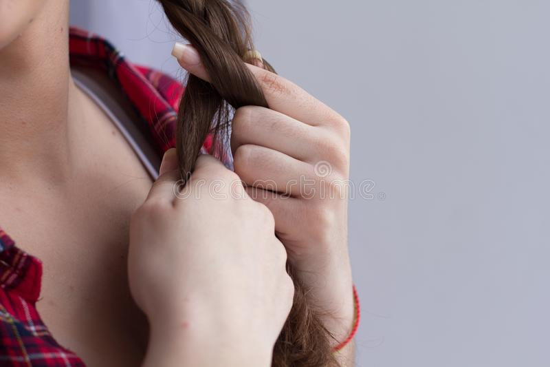 把她的头发编成辫子的女孩 免版税图库摄影