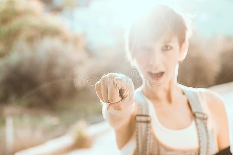把她的手指指向的女孩日落 指向照相机的妇女 免版税库存图片