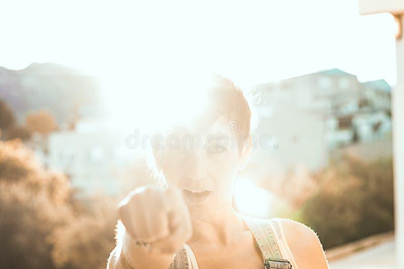 把她的手指指向的女孩日落 指向照相机的妇女 库存图片