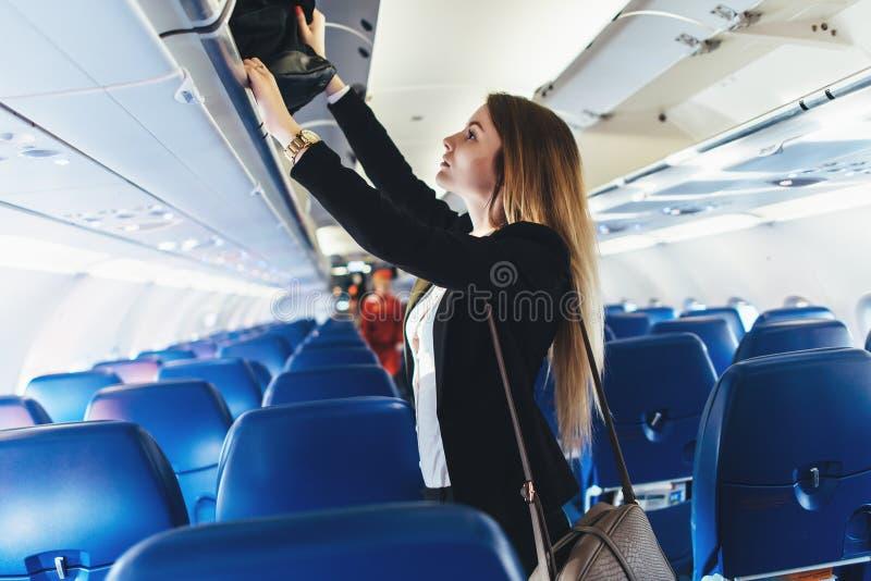 把她的手提行李放的女学生入顶上的衣物柜在飞机上 免版税库存图片