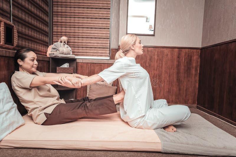 把她的腿放的好泰国妇女在她的客户上  免版税库存图片
