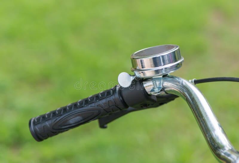把手在自然背景的自行车响铃 免版税库存图片