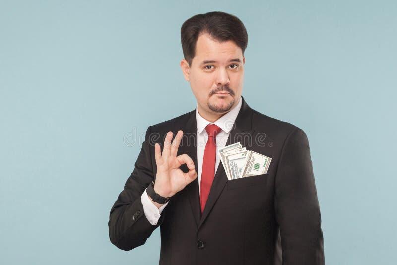 把手指指向的商人在口袋的金钱,好标志 库存照片