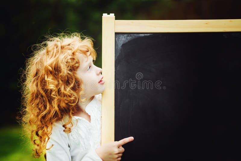 把手指指向的小女孩黑板 培训的概念 库存图片