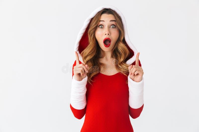 把手指指向的欧洲女孩20s佩带的圣诞节红色礼服的图象copyspace一会儿身分,被隔绝在白色 库存照片