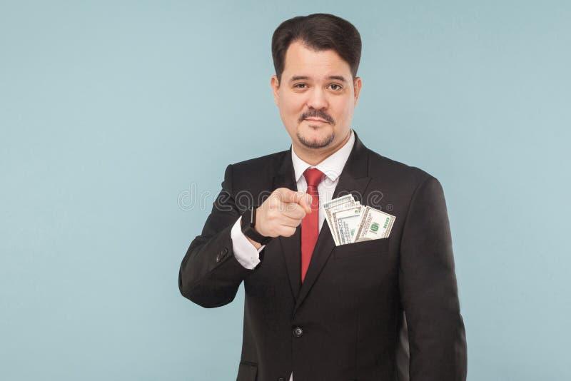 把手指指向的英俊的商人与一点微笑的照相机 库存照片