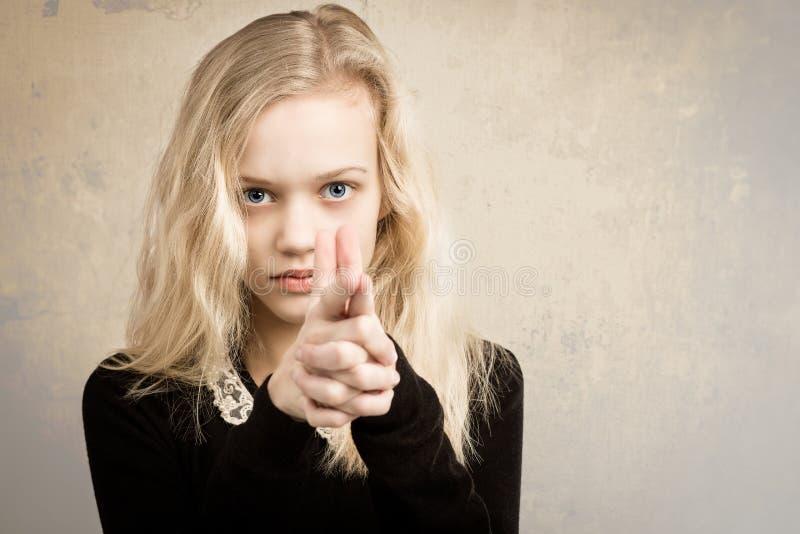 把手指枪指向的白肤金发的十几岁的女孩照相机 库存照片