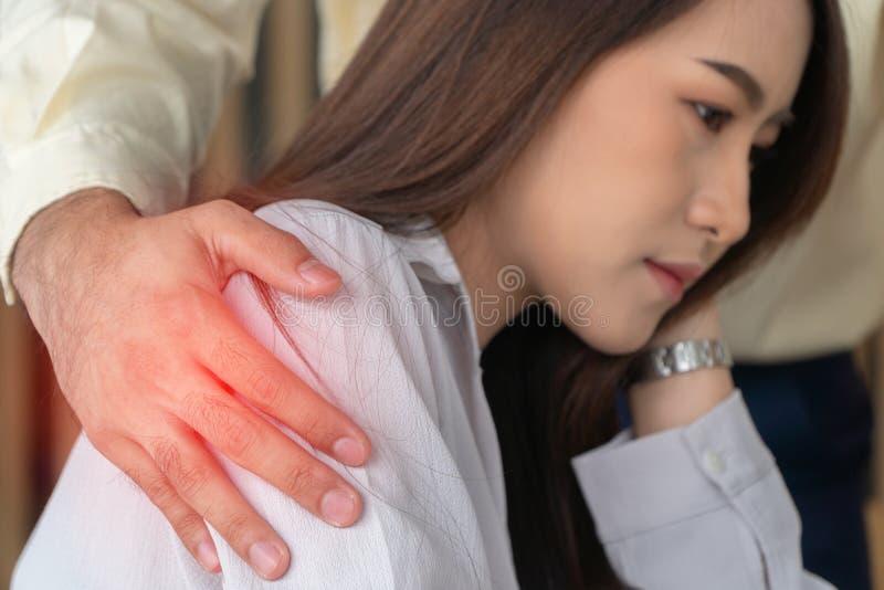 把手放的商人在女性雇员上肩膀在办公室在工作 她不快乐和感觉生气与inappropria 库存图片