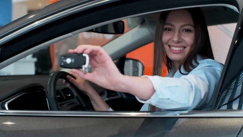 把握关键对新的汽车自动和微笑对照相机的年轻女人 免版税库存照片
