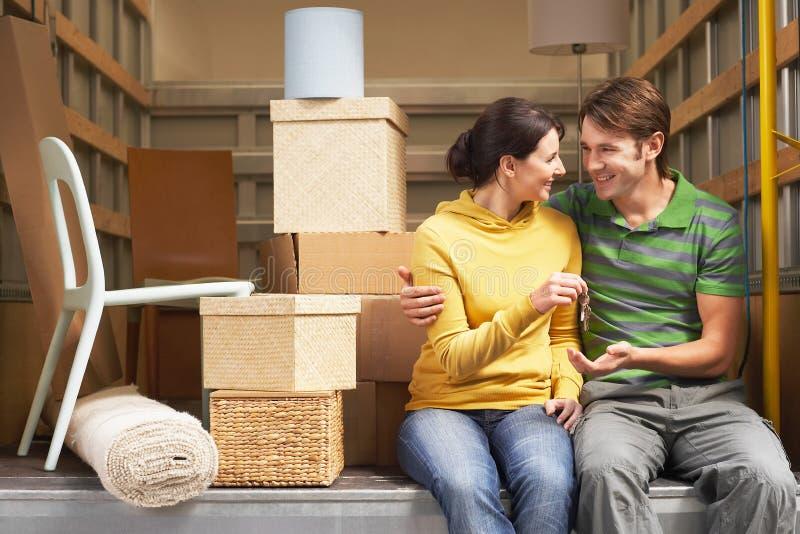 把握关键的夫妇,当松劲移动货车时 免版税库存照片