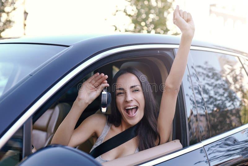 把握关键的妇女坐在新的汽车 免版税库存图片