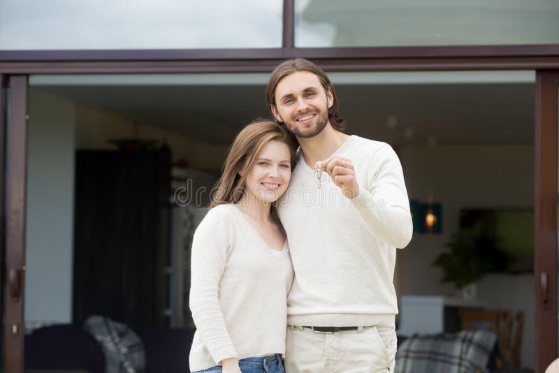 把握关键的愉快的夫妇房主站立反对新拥有ho 库存照片