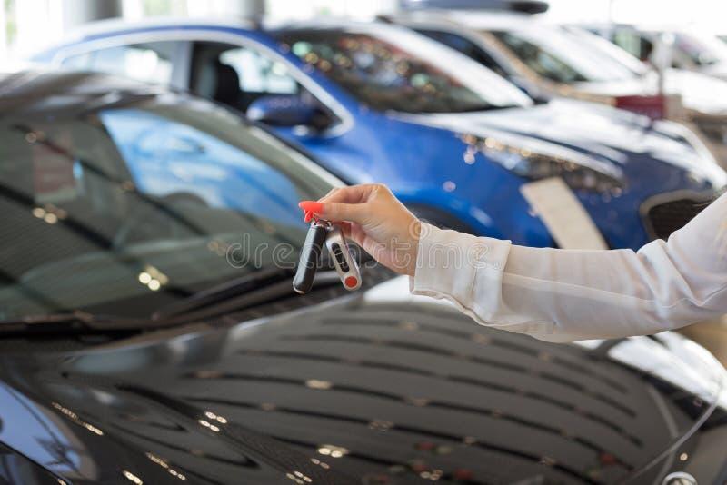 把握关键的经销商妇女对一辆新的汽车 现代和有名望的车 库存图片