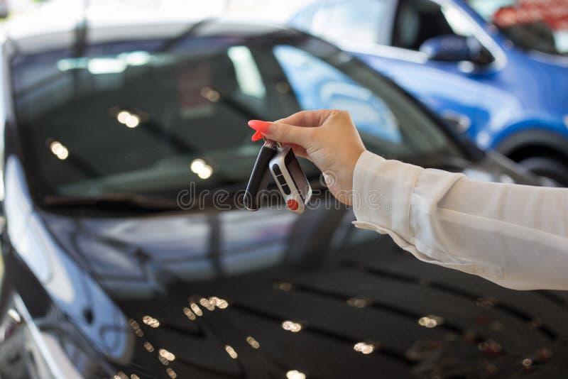 把握关键的经销商妇女对一辆新的汽车 现代和有名望的车 库存照片