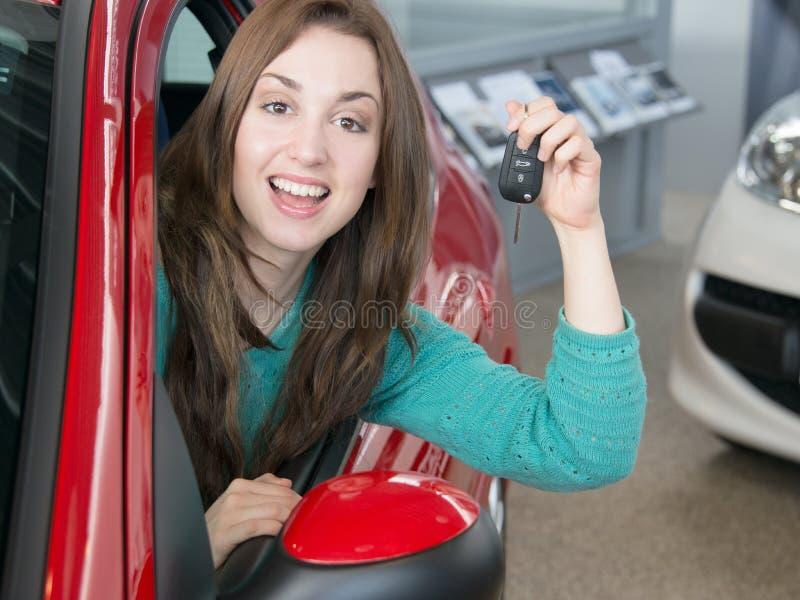 把握在售车行里面的妇女汽车关键 免版税库存图片