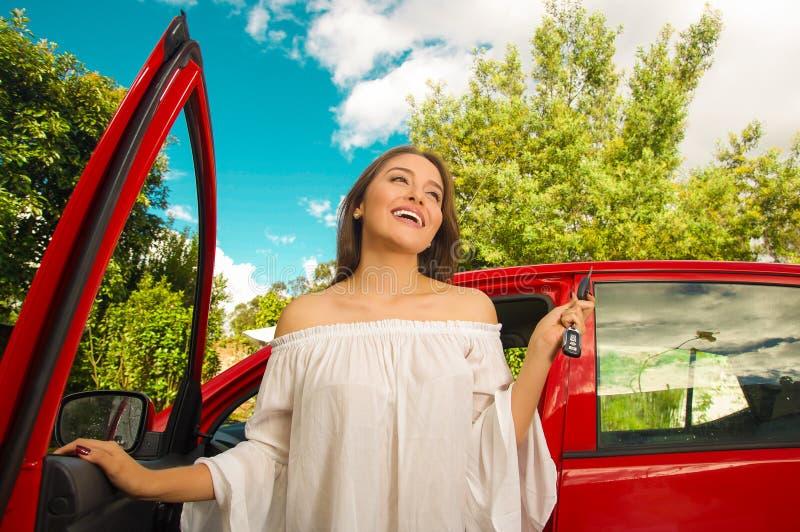 把握她的关键和微笑近对她自己的红色汽车的美丽的少妇 免版税库存照片
