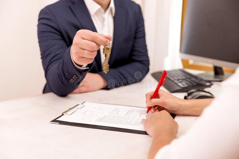 把握房子关键的房地产开发商对他的客户在签合同,房地产的,移动的家概念或租赁物产以后 免版税库存图片