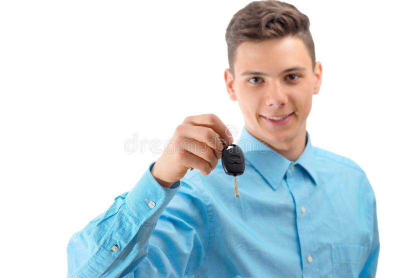 把握汽车关键的可爱的十几岁的男孩被隔绝在白色 免版税库存图片