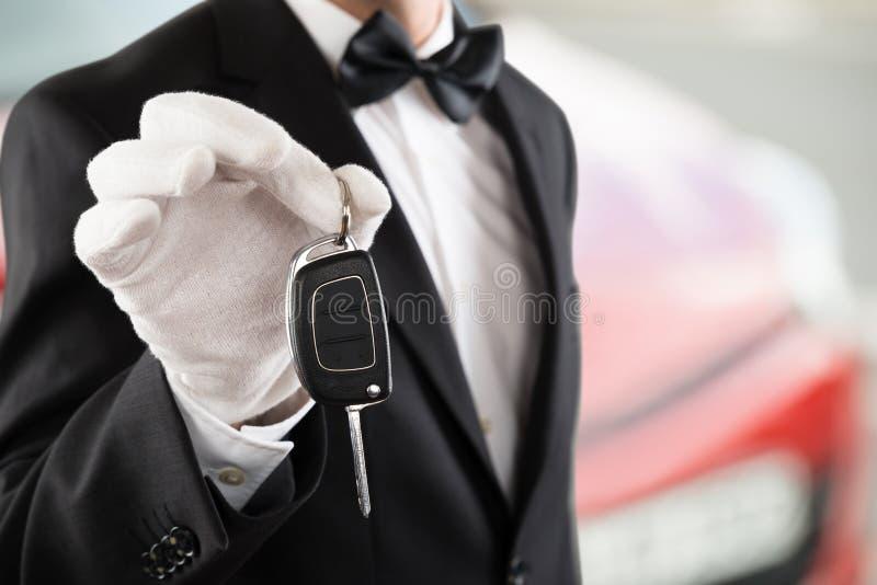 把握汽车关键的服务员男孩 免版税库存图片