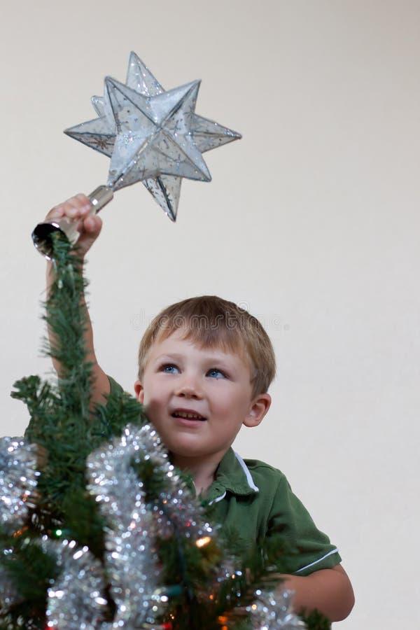 把星形放的男孩在圣诞树上 免版税库存照片