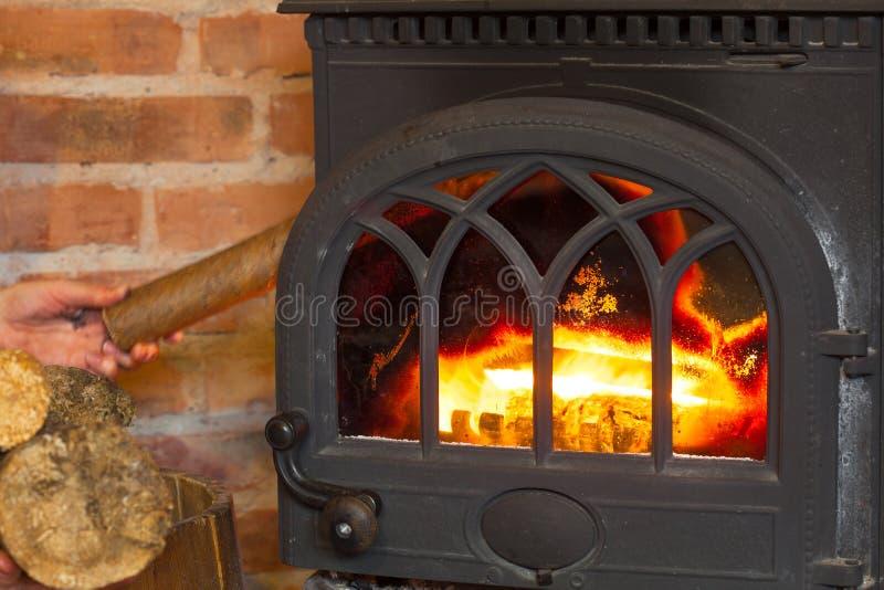 把木头放的手在火壁炉上 热化 图库摄影
