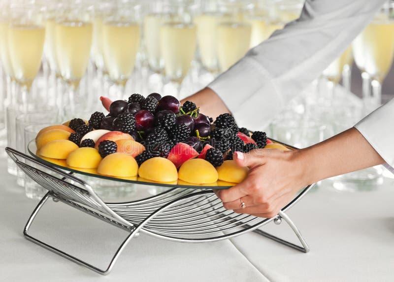 把果子盘子放的侍者在桌上在党 库存图片