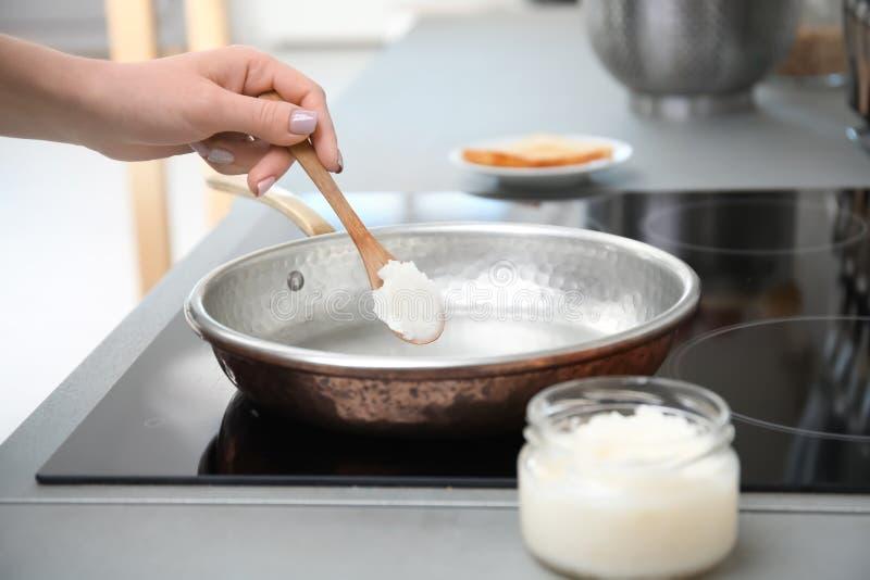 把椰子油放的妇女在煎锅上在厨房 免版税库存照片