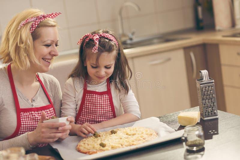 把橄榄放的小女孩在薄饼上 免版税库存图片