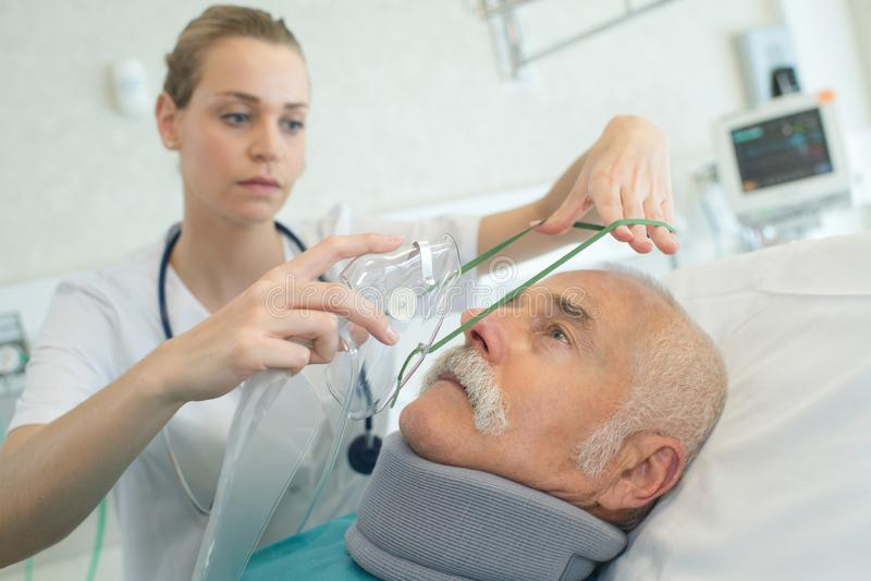 把氧气面罩放的年轻女性麻醉师在资深患者上 库存图片