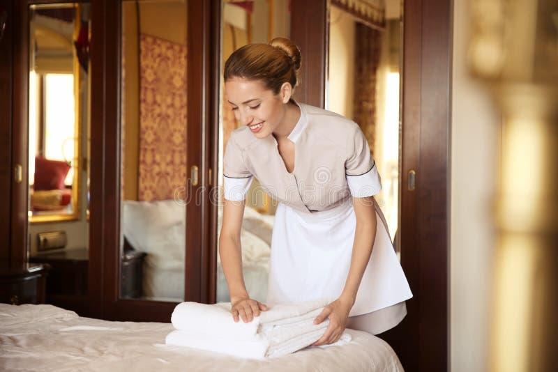 把清洁毛巾放的女服务生在床上 免版税库存照片
