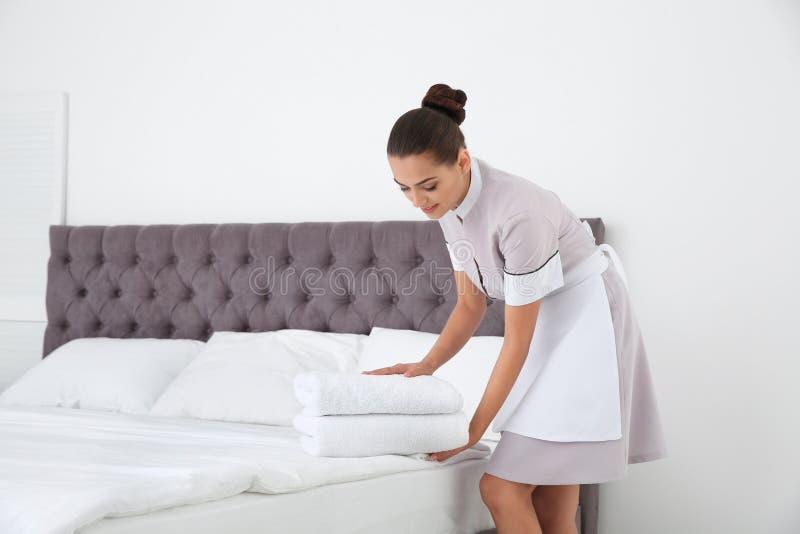把清洁毛巾放的年轻女服务生在床上 库存照片