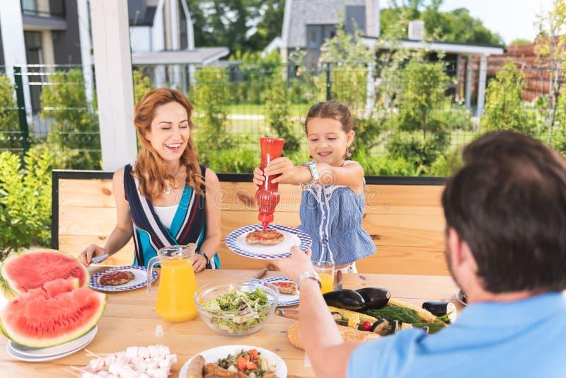 把番茄酱放的宜人的好女孩在肉上 免版税库存图片