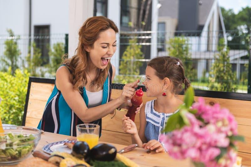 把番茄酱放的正面快乐的妇女在她的女儿上引导 免版税图库摄影