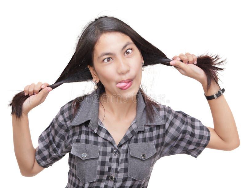 把疯狂的女孩幽默拉编成辫子 免版税库存照片