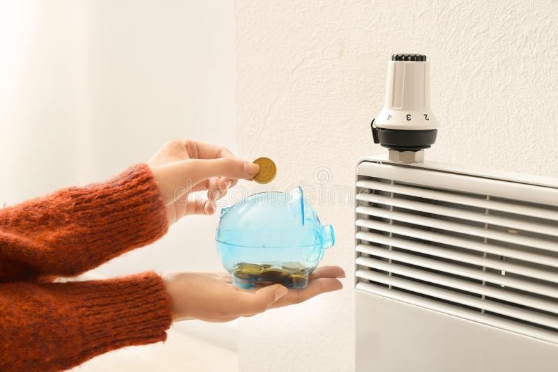 把硬币放的妇女入存钱罐在温箱附近在calorifer上 加热的保存的概念 免版税库存照片