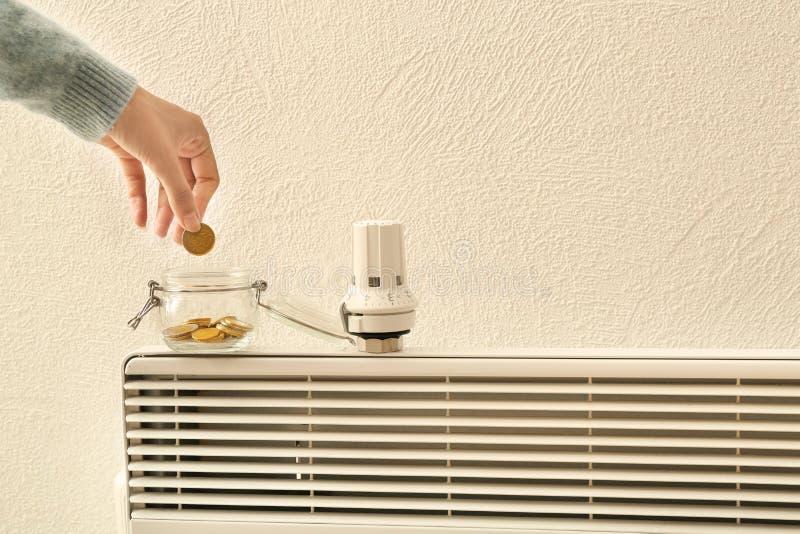 把硬币放的妇女入玻璃瓶子在温箱附近在calorifer上 加热的保存的概念 图库摄影