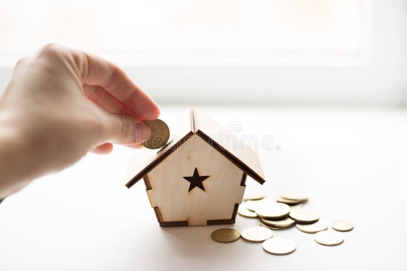 把硬币放的手特写镜头在木屋存钱罐中在白色背景上 安置文本 攒钱,房屋贷款,抵押,a 库存照片