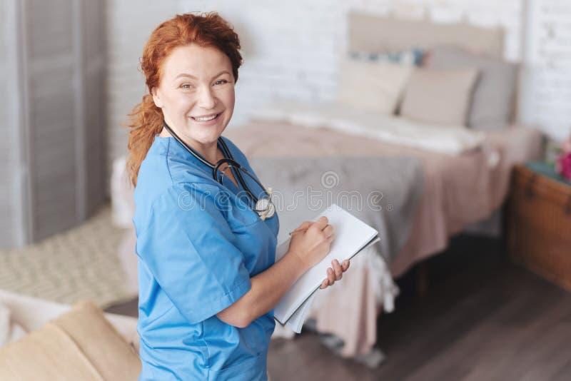 把笔记拿回家的激动的女性医护人员在患者 图库摄影