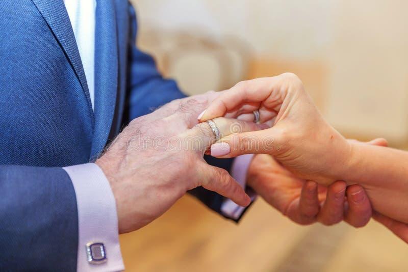 把结婚戒指放的新娘手在新郎手指上 图库摄影