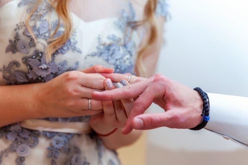 把结婚戒指放的新娘手在新郎手指上 库存照片