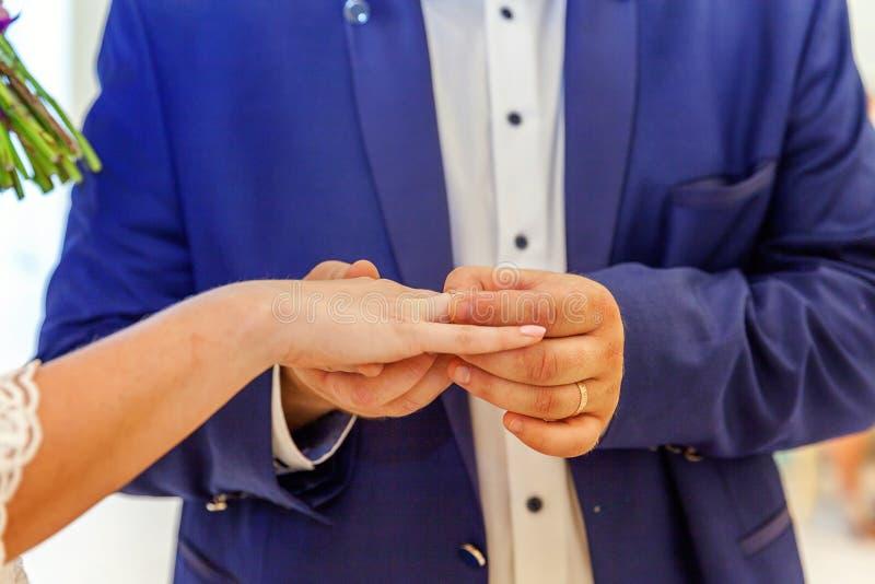 把结婚戒指放的新郎手在新娘手指上 库存照片