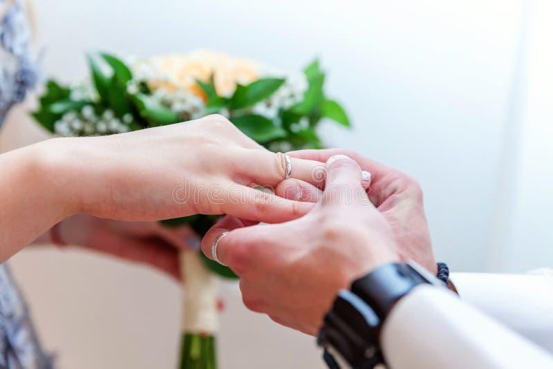 把结婚戒指放的新郎手在新娘手指上 免版税图库摄影