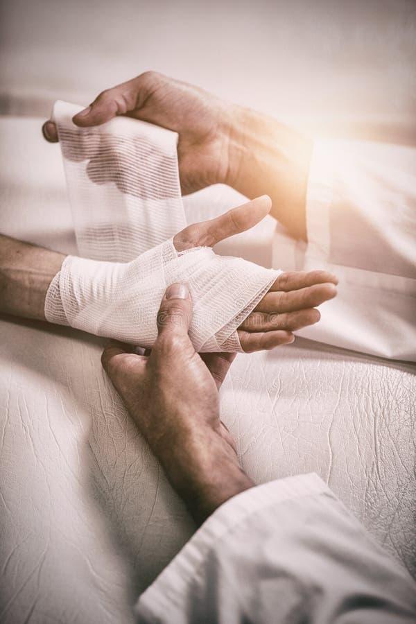 把绷带放的生理治疗师在患者的受伤的手上 免版税库存图片